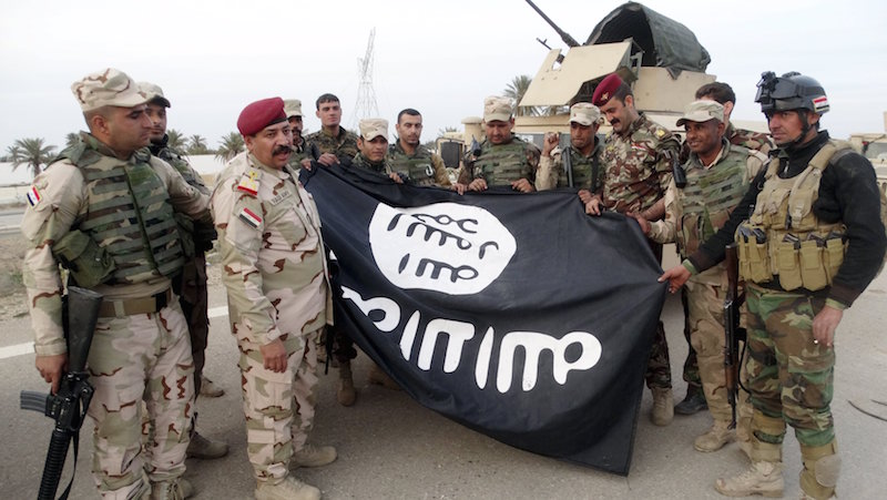 Iraqi security forces stand with an Islamic State flag which they pulled down in the city of Ramadi